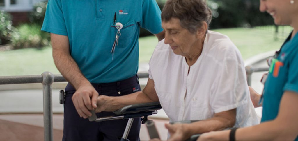 Elderly Patient with Nurses Helping