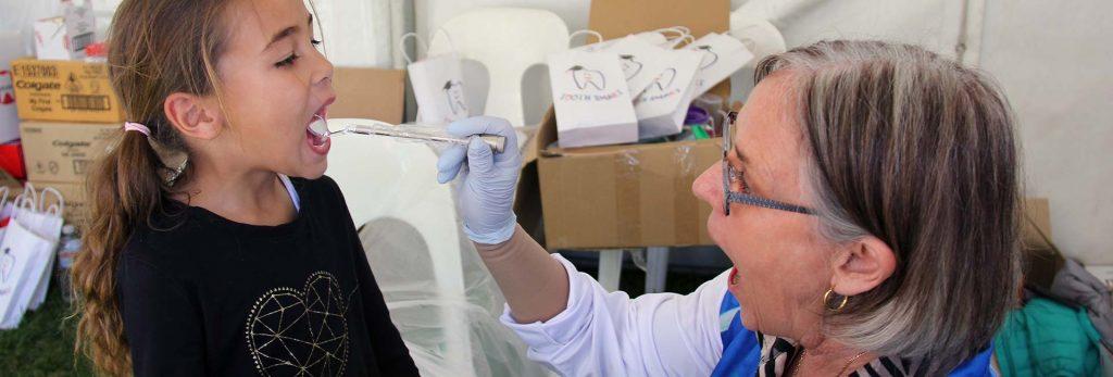 Dental Nurse checking girl's teeth